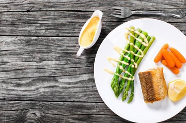 Hake served with asparagus, piece of lemon, baby carrots and hollandaise sauce on a white platter atop an old rustic table