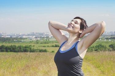Smiling fitness plus size woman enjoy sunlight