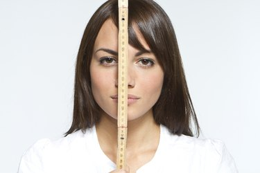 woman holding tape measure in front of face