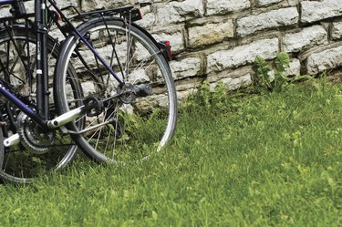 Close-up of bicycle parked on the grass against a brick wall