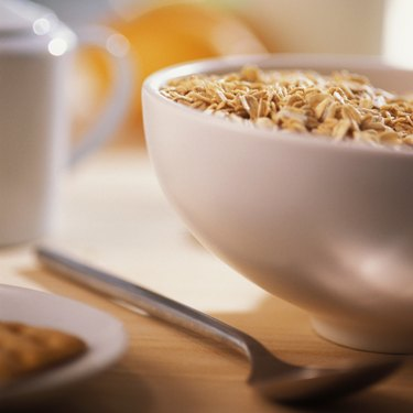 Bowl of cereal with spoon and edge of plate with pastry on it, close-up