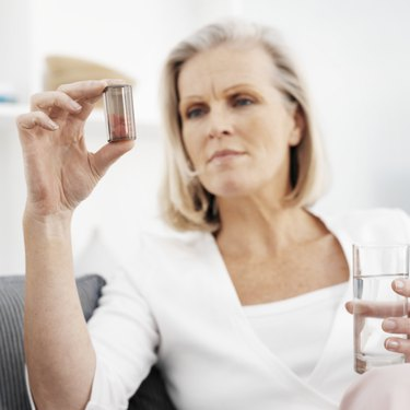 Mature woman on sofa, holding pills and glass of water (focus on foreground)