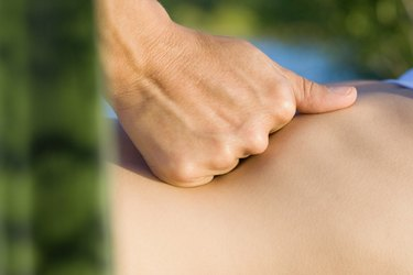 Massage therapist's hand on patient's abdomen, close-up
