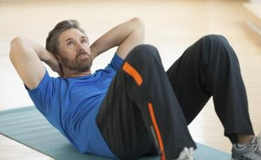 Mature man doing sit-ups on exercise mat at home