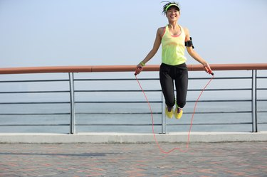 young fitness woman jumping rope at  seaside