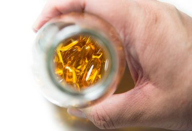 Male hand hold bottle of fish oil over white