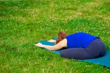 Young woman doing yoga by the lake, located on the docks.  Concept healthy lifestyle. Lots of copy space.