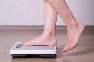 A woman's feet stepping onto a bathroom scale