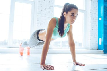 Full length of young beautiful woman in sportswear doing plank while standing in front of window at gym