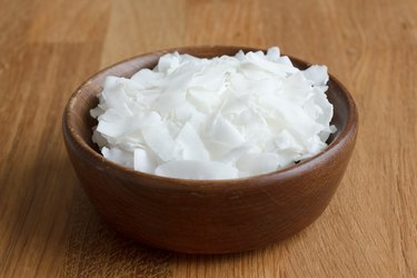 Dark bowl of shaved coconut on wood table.