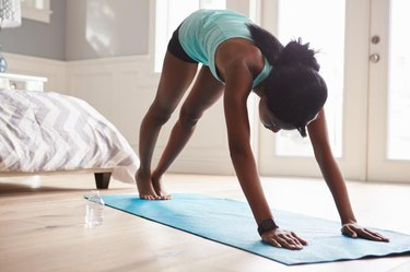 Young black woman in the downward-facing dog yoga pose