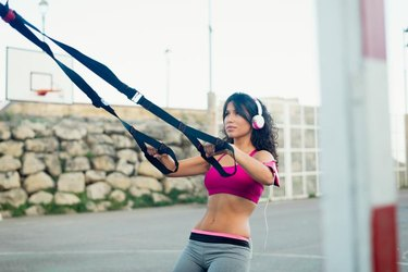 Motivated woman doing pull row urban training for back and arms with fitness straps. Healthy outdoor fitness workout for strength and body conditioning.