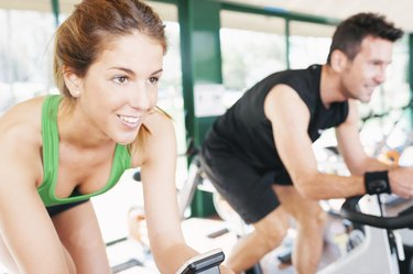 Athletes using the stationary bicycle in a gym