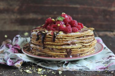 Stack of freshly baked pancakes with chocolate sauce and raspberry