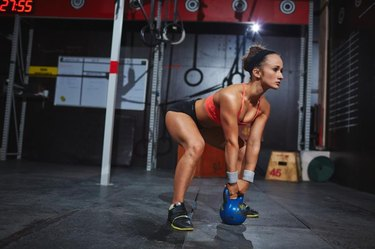Strong young female working out with kettle