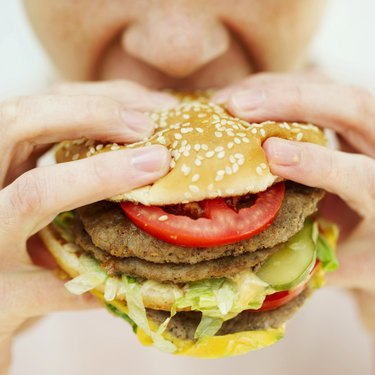 Close-up of a woman eating a hamburger