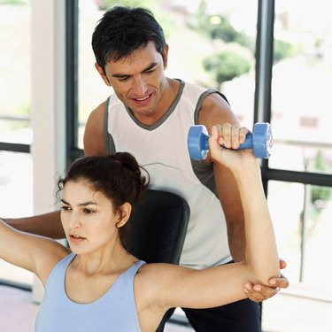 close-up of an instructor training a woman with dumbbells
