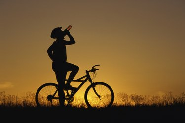 Silhouette of a man drinking water on a bicycle