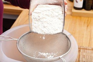 Put flour of glass bowl through a sieve