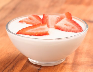 full bowl of yogurt with strawberries on wood
