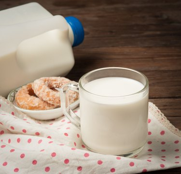 Glass of milk with doughnut on wood
