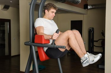 Handsome young man doing lats pull-down workout in gym