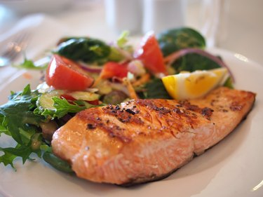 Plate of broiled salmon with asparagus and salad