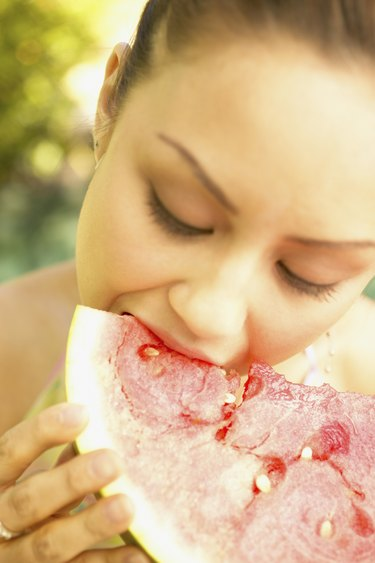 Young woman eating a watermelon slice