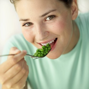 Close-up of a woman eating peas with a fork