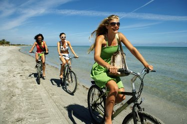 Three young women riding bicycles on beach, smiling