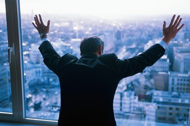 Businessman leaning against window, arms raised