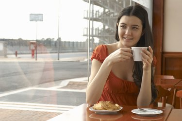 Young woman in cafe holding coffee cup smiling, portrait