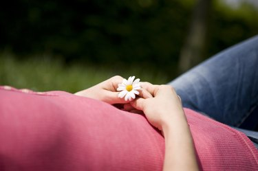 A woman lying on the grass, holding a daisy, cropped