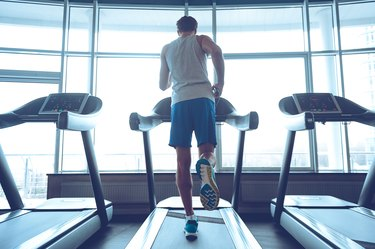 Full-length rear view of young man in sportswear running on treadmill in front of window at gym