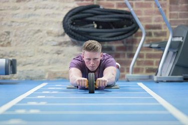 Young man training his abs on the ab roller in the gym.