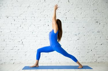 Young attractive woman practicing yoga, standing in Virabhadrasana 1 exercise, Warrior one pose, working out, wearing sportswear, blue suit, indoor full length, white loft studio background