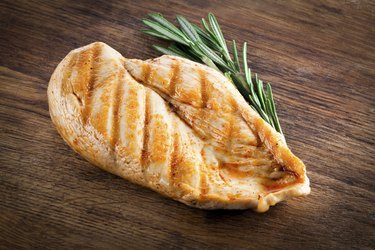 Grilled organic chicken with rosemary on wood