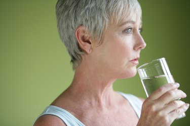 Mature adult with glass of water.