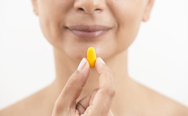 Woman Holding And Showing Yellow Pill