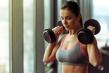 Attractive young woman working out with dumbbells in gym