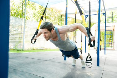 Man during workout with suspension straps on the street