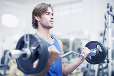 Man lifting barbell in gymnasium