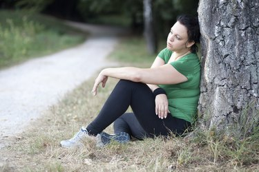 Tired overweight woman sitting by the tree