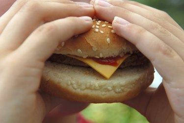 Close-up of a person's hands holding a cheeseburger