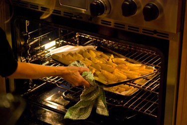 Woman lifting a tray of potato wedges into oven