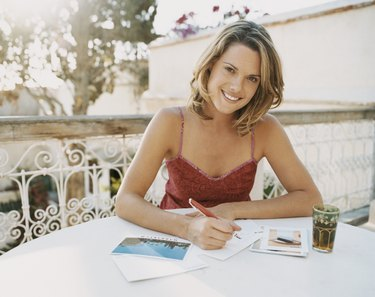 Woman Sitting at an Outdoor Table Writing Postcards