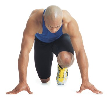 a young bald black male runner wears a blue tank top and leans forward in the starting position