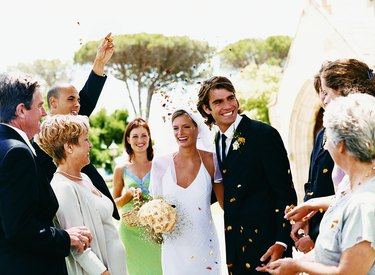 People Throwing Confetti Over a Newlywed Couple Leaving Church