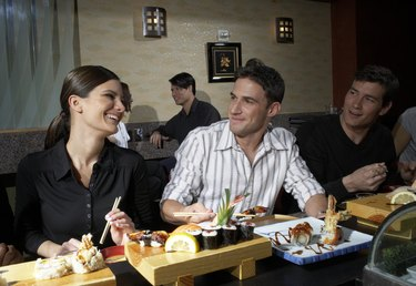 People in sushi bar, man and woman flirting