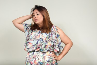 Portrait of stressed beautiful overweight Asian woman